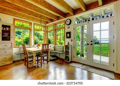 Vintage style dining room with large wood beams and glass door.Wood beam ceiling and hardwood floor.