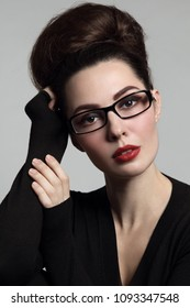Vintage style glamorous portrait of young beautiful woman in glasses