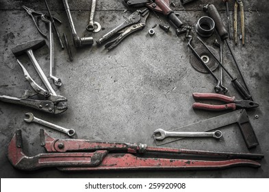 Vintage style image of blank space on concrete floor which have a lot of old tools as props in the scene