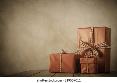 Vintage style image of gifts wrapped in paper and tied with gingham ribbon on a wood planked table with parchment background and vignette.  brown and coral tones with copy space to left and above.