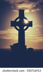 Vintage Style Image Of Sun Glinting Through A Celtic Cross Gravestone