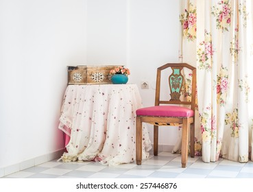 Vintage style interior with table, carved chair and floral curtain