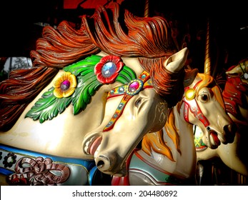 Vintage style nostalgic carousel riding horse carved head on an old fashioned merry go round ride at the fairground amusement park