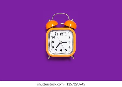 Vintage style orange metal alarm clock with bells standing on the purple surface isolated. back to school concept. free space for text