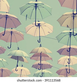 Vintage style photo of colorful umbrellas floating magically in the sunny blue sky above the street. Toned vintage colors