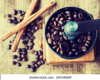 Vintage style photo of the roasted coffee beans in a coffee grinder with blur cinnamon and coffee beans background.