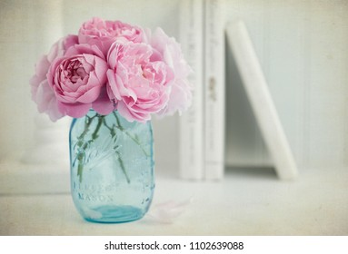 Vintage style photograph of a bouquet of pink English roses in a turquoise blue mason jar