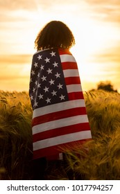 Vintage style photograph of mixed race African American girl teenager female young woman in a field of wheat or barley crops wrapped in USA stars and stripes flag in golden sunset evening sunshine