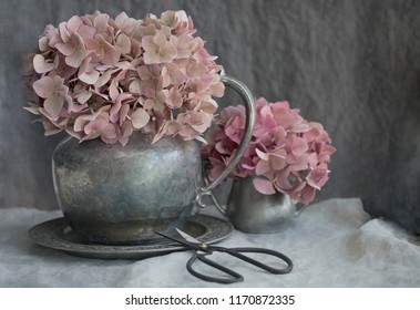Vintage style photograph of pink hydrangea blooms in pewter vases on gray