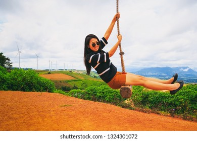 Vintage style photography of pretty Asian girl play giant swing in wind turbine power generator park.