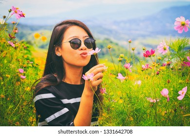 Vintage style photography of pretty Asian girl in cosmos flower park.