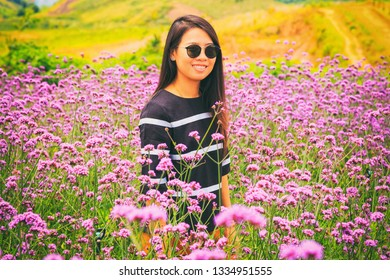 Vintage style photography of pretty Asian girl in verbena flower park.