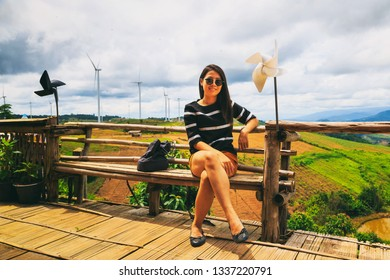 Vintage style photography of pretty Asian girl in wind turbine power generator park.