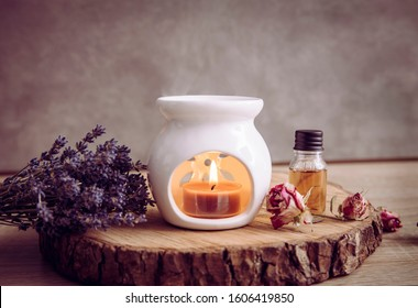 Vintage style picture of white ceramic candle aroma oil lamp with essential oil bottle and dry flower petals on natural pine wood disc, dry background with copy space.