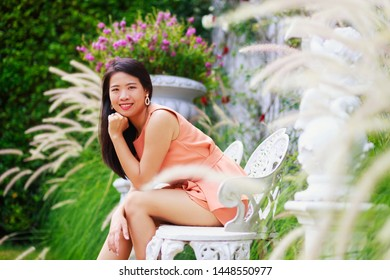 Vintage style portrait photography of pretty Asian girl in flower park, selected focus.