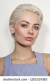 Vintage style portrait of young beautiful tanned blond woman in striped top