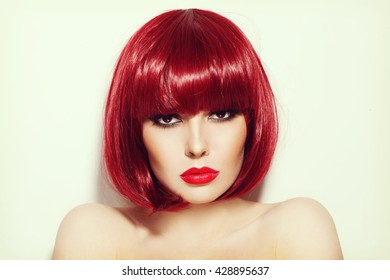 Vintage style portrait of young beautiful sexy red-haired girl with bob haircut and stylish make-up