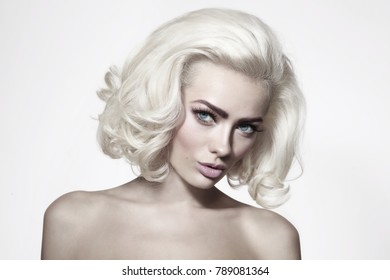 Vintage style portrait of young beautiful woman with platinum blonde hair and fresh make-up