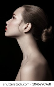 Vintage style profile portrait of young beautiful woman with hair bun