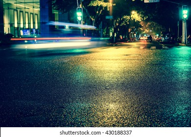 Vintage style - Rainy night in the big city, light from the shop windows reflected on the road on which cars travel. View from the level of asphalt