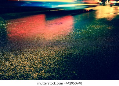 Vintage style - Rainy night in the big city, the light from the headlamps of vehicles approaching on the road. Close up view from the level of asphalt, focus on the asphalt
