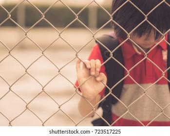 Vintage style of sad boy behind fence mesh netting. Emotions concept - sadness, sorrow, melancholy.