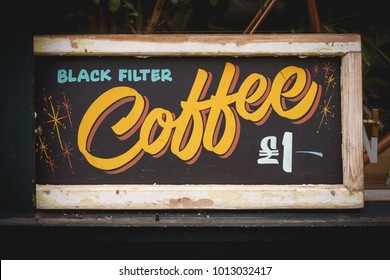 Vintage style sign for black filtered coffee on a blackboard with a wooden frame. Landscape format.