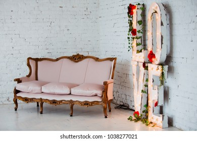 Vintage style sofa decorated with flowers in loft interior room with big window.