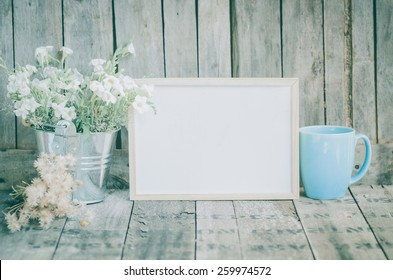 Vintage style White flowers stainless pot and blue pastel tea cup on wooden background, still life