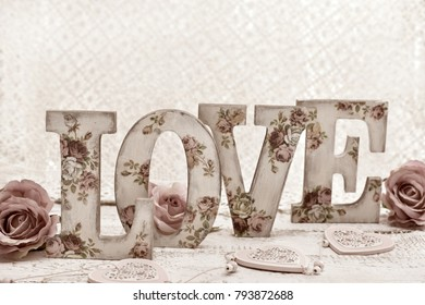 vintage style wooden letters LOVE with rose pattern decoupage decoration standing on wooden table