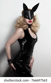 Vintage style young slim sexy woman in black vynil dress and fetish leather rabbit mask