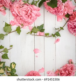 vintage styled image of pink roses lying on white wooden background, with copy space, inspired by flat lay style