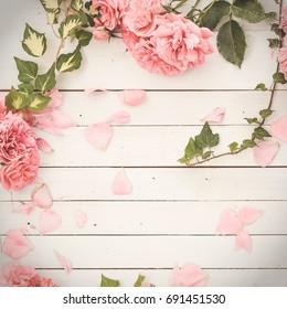vintage styled image of pink roses lying on white wooden background, with copy space, inspired by flat lay style with matte effect