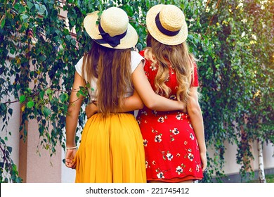 Vintage styled outdoor lifestyle fashion image of two pretty girls guys at city park, wearing retro hipster elegant dresses and straw hats. Bright instagram colors.