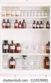 Vintage stylish glass bottles with pharmaceutical substances on the shelf in old pharmacy