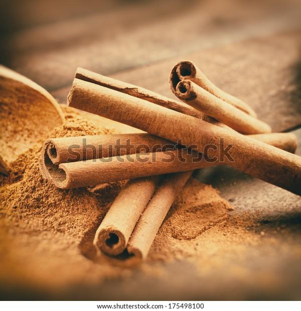 Fotografía estilizada de época de palos de canela y polvo de canela sobre tablas de madera