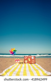Vintage suitcase and beach items against blue sea and sky background. Summer vacation concept