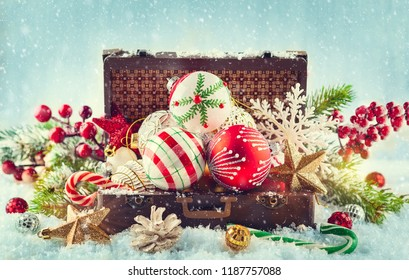 Vintage suitcase with festive Christmas decorations for the Christmas tree in snow