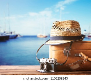 Vintage suitcase, hipster hat, photo camera and passport on wooden dack. Tropical sea, beach and yachts in background. Summer holiday  and cruise traveling concept.