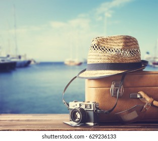 Vintage suitcase, hipster hat, photo camera and passport on wooden deck. Tropical sea, beach and yachts in background. Summer holiday  and cruise traveling concept.