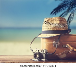 Vintage suitcase, hipster hat, photo camera and passport on wooden deck. Tropical sea, beach and palm three in background. Summer holiday traveling design concept.