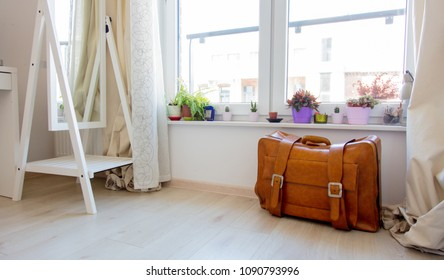 Vintage suitcase liyng down on floor with clothes inside before a summer travel