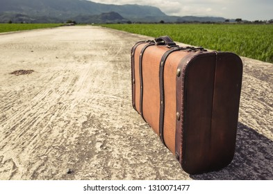 vintage suitcase on the road with nobody in the countryside