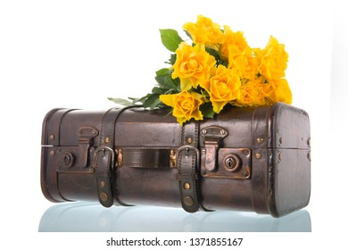 Vintage suitcase with yellow roses isolated over white background