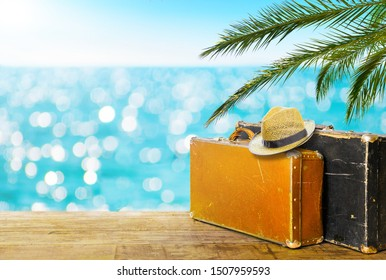 Vintage suitcases, straw sun hat on wooden deck. Tropical sea and palm leaves in background. Travel vacation background with copy space