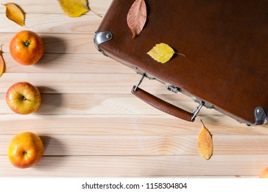 Vintage suitecase, ripe apples and colorful leaves on the wooden background. Autumn trip. Harvest. Flat lay. Space for text