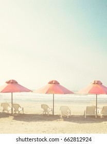 Vintage summer beach with pink pastel parasols