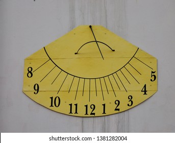 A vintage sundial throws a long shadow, tracking the motion of the sun while telling the time of day. Sundial clock with digits