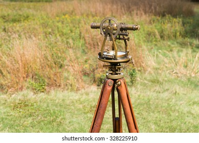 Vintage Surveyor's Level (Transit, Theodolite) with wooden Tripod in a field.