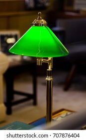 Vintage switched on green lamp on desk in reading lawyers room. Vertical close up crop